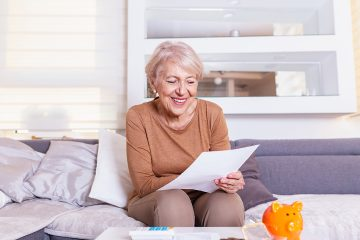 Senior woman smilling and happy about her finances. Old lady receives a letter.Senior lady receiving good news from a paper mail.